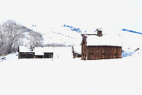 An old barn and outbuildings east of Gunnison, Colorado enveloped in the white of winter.