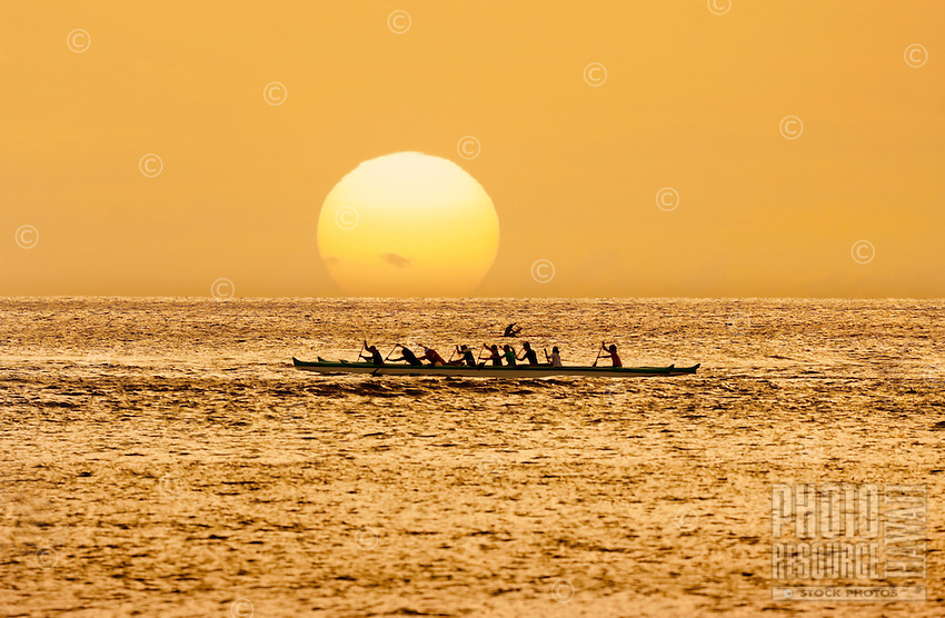 At sunset, a group paddles an outrigger canoe in open ocean off of O'ahu.