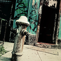 A water hydrant seen in front of a house made of wood and sheet metal on the street of San Salvador, El Salvador, 21 December 2013.