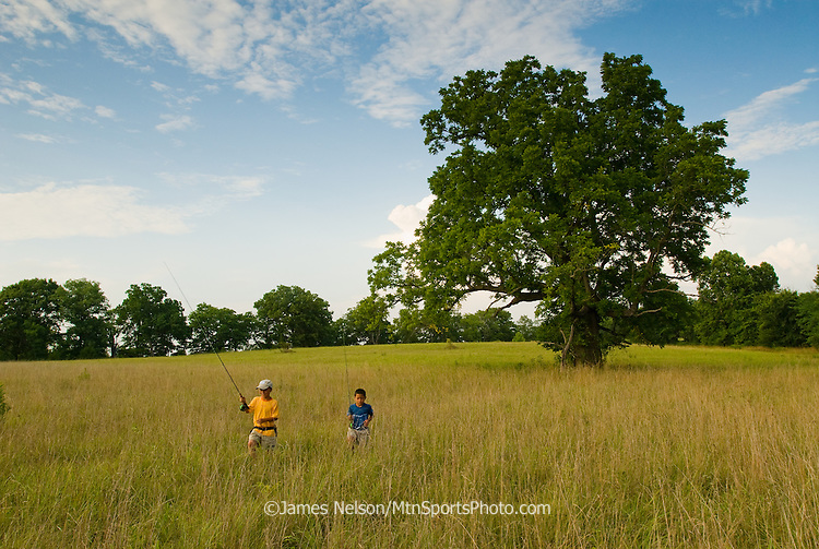 Eight- and six-year-old brothers with fly rods walk to a fishing run on the James River in the Ozark Mountains, Missouri.