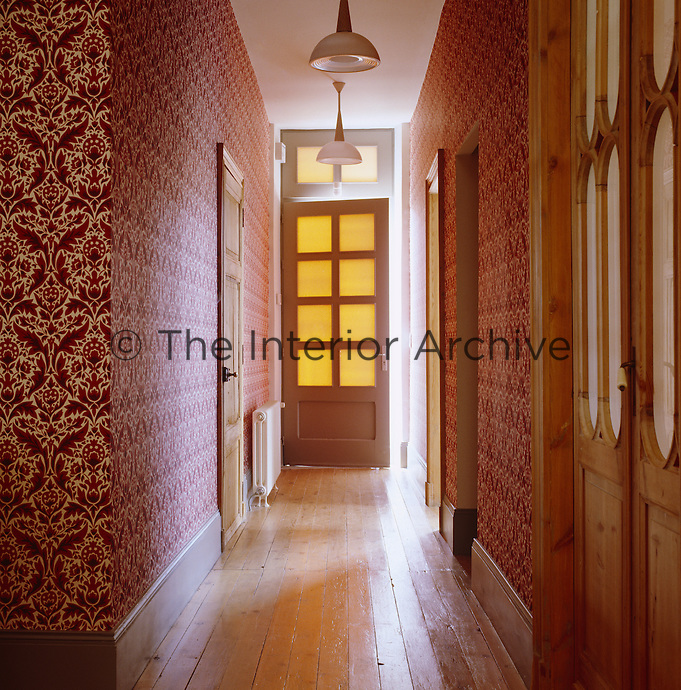 The hallway is covered in a modern take on damask designed for the house by Eley Kishimoto.
