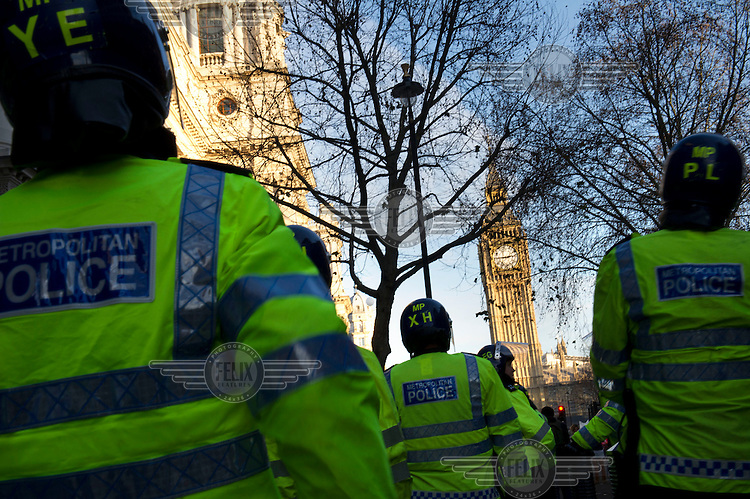 Riot police wait near Parliament Square, London during a demonstration by students against the government's proposed increase in university tuition fees.