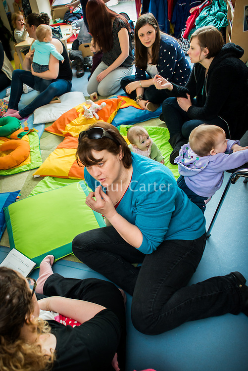 A breastfeeding consultant giving advice to a mother who is breastfeeding her baby at a drop-in breastfeeding support centre.<br /> <br /> Image from the &quot;We Do It In Public&quot; documentary photography project collection: <br />  www.breastfeedinginpublic.co.uk<br /> <br /> Dorset, England, UK<br /> 17/04/2013