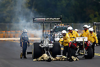 Sep 15, 2013; Charlotte, NC, USA; Safety safari crews tend to NHRA top fuel dragster driver Brittany Force (left) after a fire during the Carolina Nationals at zMax Dragway. Mandatory Credit: Mark J. Rebilas-
