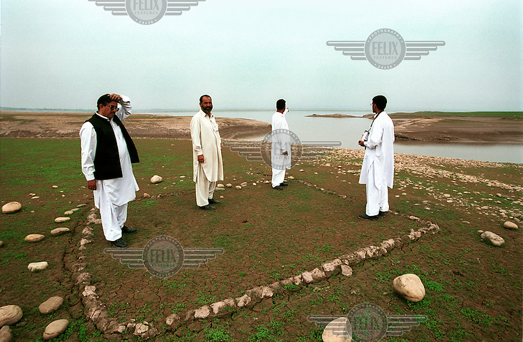 Men having returned from Britain visit the site of a house in their former village which was submerged in the reservoir created by the Mangla Dam.  The Mangla dam project in the 1960s displaced over 100,000 people when water innundated surrounding settlements.  In the dry season Old Dudial re-emerges as the water in the reservoir recedes...