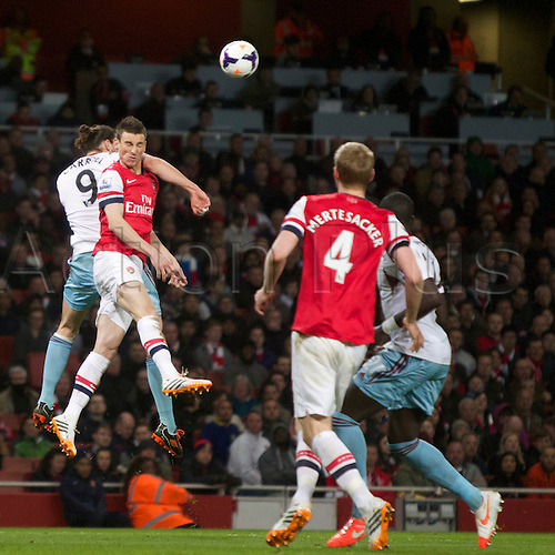 15.04.2014.  London, England. Laurent Koscielny of Arsenal battles with Andy Carroll of West Ham United during the Barclays Premier League match between Arsenal and West Ham from the Emirates Stadium.
