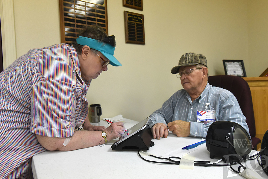 NWA Democrat-Gazette/FLIP PUTTHOFF<br />Audrey Oakes (left) signs in to vote Tuesday July 11 2017 in Avoca with poll worker Marvin Farar (cq). An election regarding Sunday liquor sales was held in Avoca.