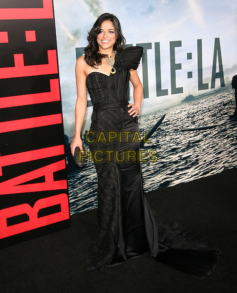 "MICHELLE RODRIGUEZ.Premiere of ""Battle: Los Angeles"" held at The Grauman's Chinese Theatre in Hollywood, California, USA. .March 8th, 2011 .full length black one shoulder dress fishtail hand on hip clutch bag .CAP/RKE/DVS.©DVS/RockinExposures/Capital Pictures."