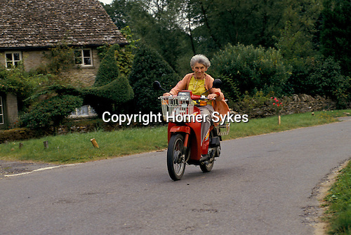 'ENGLISH VILLAGE FETE', MRS JEAN STEEL GOES ABOUT HER BUSINESS IN THE VILLAGE ON HER SCOOTER.