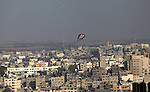 A kite with Palestinian flag colors is seen flying over Gaza City on July 07, 2014. Israeli air strikes on Gaza, that killed at least seven Palestinian militants overnight, came after a day in which armed groups fired at least 25 rockets and mortar rounds at southern Israel. The Gaza violence came as violence raged across annexed east Jerusalem and Arab towns in Israel following the kidnap and murder of a Palestinian teenager in a suspected revenge attack by Jewish extremists who burned him alive. Photo by Ashraf Amra