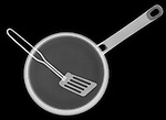 X-ray image of a frying pan with turner (white on black) by Jim Wehtje, specialist in x-ray art and design images.