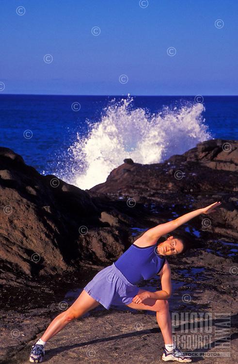 Woman doing yoga near Halona blow hole, Oahu