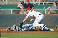 Brandon Grudzielanek (21) of the Lansing Lugnuts reaches for a wild pick-off throw as Jhonny Bethencourt (6) of the South Bend Cubs dives back towards first base at Cooley Law School Stadium on June 15, 2018 in Lansing, Michigan. The Lugnuts defeated the Cubs 6-4.  (Brian Westerholt/Four Seam Images)