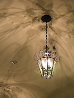 Fine art abstract of lantern, with 4 candle bulbs, hanging from ceiling by link cable, with shadows from lamp creating lovely, arcing, varied shadows on ceiling above.
