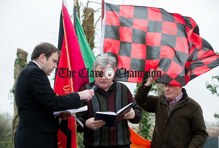 Fr Tom Carroll addresses the gathering watched by Councillor Cathal Crowe  as local man Johnny White does battle with the wind during the Wreath laying Ceremony at the Republican Plot in Meelick Graveyard on Easter Sunday. Photograph by John Kelly.