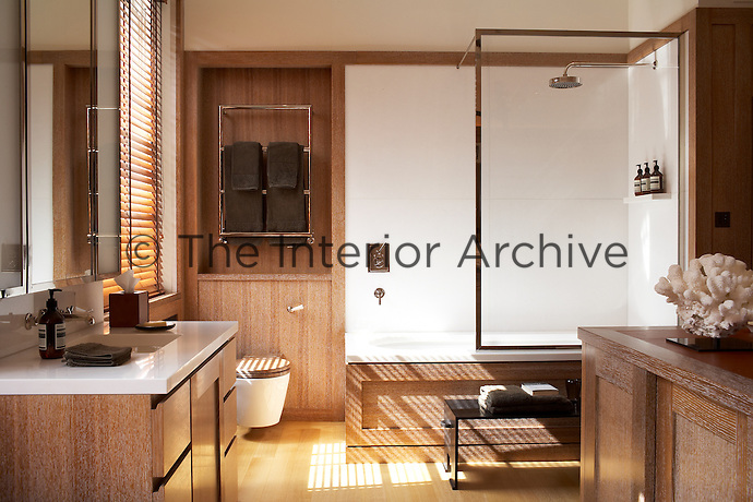 This wood-panelled bathroom has a clear glass shower screen and a towel rack fitted into the alcove