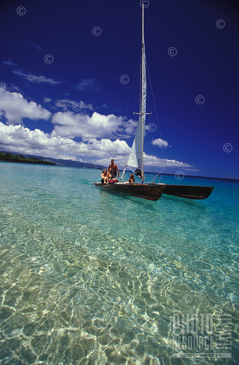 Group of young people sailing catamaran in clear water off sandy beach of Waimea Bay, North Shore, Oahu