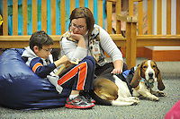 NWA Democrat-Gazette/Michael Woods --01/14/2015-- w @NWAMICHAELW... Luis Cruz, age 9 from Springdale, reads a book to Erin Renollet Children's Assistant with the Springdale Public Library and Banjo, a therapy dog, during Wednesday evenings session of the Kibbles and Books program at the Springdale Public Library. Kibbles & Books is a literacy program designed to build confidence in young readers by reading out loud to therapy dogs giving the children a chance to practice their literacy skills in a stress-free and fun context.