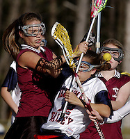 Merrimack Valley's Kortnie Winters, center, collides with Portsmouth's Whitney Dupriey, left, and Britt Conway during a lacrosse match at Merrimack Valley High School..