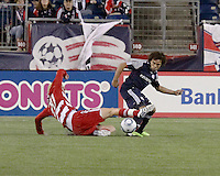 FC Dallas midfielder/forward Brek Shea(20) attempts to kick the ball free after being tackled by New England Revolution defender Kevin Alston (30).  The New England Revolution drew FC Dallas 1-1, at Gillette Stadium on May 1, 2010