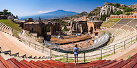 Panoramic photo of a tourist visiting Teatro Greco aka Taormina Greek Theatre, with Mount Etna Volcano behind, Sicily, Italy, Europe. This is a panoramic photo of a tourist visiting Teatro Greco aka Taormina Greek Theatre, with Mount Etna Volcano behind, Sicily, Italy, Europe.
