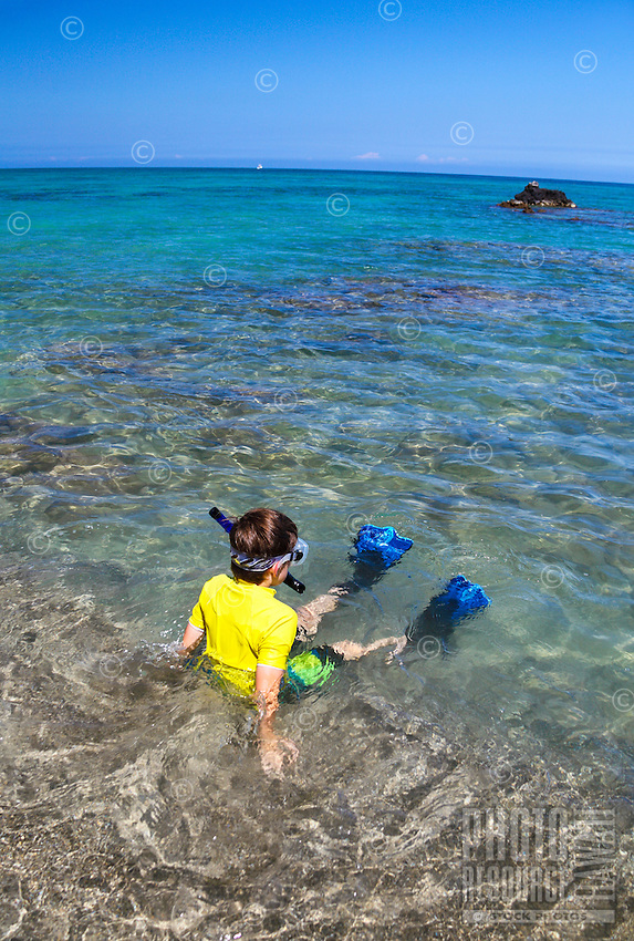 A young snorkeler relaxes in the clear waters of 'Anaeho'omalu Bay, Big Island.