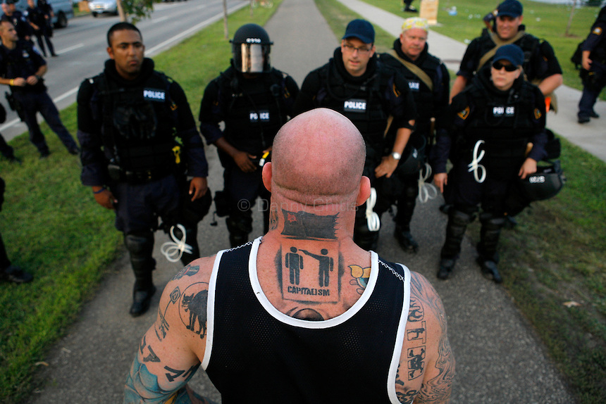 """Submission wrestler and alleged anarchist Jeff """"The Snowman"""" Monson approaches police about their blockade of a major road leading to downtown St. Paul. Thousands of activists protested the 2008 Republican National Convention in St. Paul, MN from September 1-4. While some marches were peaceful, others led to violence by both the protesters and riot police."""