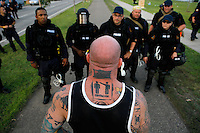 "Submission wrestler and alleged anarchist Jeff ""The Snowman"" Monson approaches police about their blockade of a major road leading to downtown St. Paul. Thousands of activists protested the 2008 Republican National Convention in St. Paul, MN from September 1-4. While some marches were peaceful, others led to violence by both the protesters and riot police."