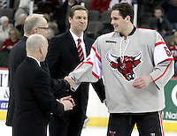UNO senior Pasko Skarica shakes hands with UNO Chancellor John Christensen as UNO Associate Athletic Director Mike Kemp (left) and UNO Athletic Director Trev Alberts look on during a ceremony honoring the team's seniors. Denver beat Nebraska-Omaha 4-2 Saturday night at Qwest Center Omaha. (Photo by Michelle Bishop).