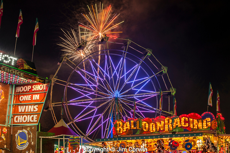 Evergreen State Fair fireworks display with ferris wheel and game booths at night
