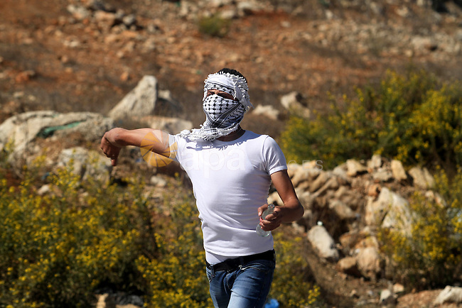 A Palestinian protester throws stones towards Israeli security forces during clashes at a protest to show solidarity with al-Aqsa mosque, outside Israel's Ofer military prison near the West Bank city of Ramallah October 21, 2014. A Palestinian official on Monday called for holding an emergency Arab and Islamic summit to discuss Israeli plans to divide the Al-Aqsa Mosque compound between Jews and Muslims. In recent months, groups of Jewish settlers accompanied by Israeli security forces have repeatedly forced their way into East Jerusalem's flashpoint Al-Aqsa Mosque complex. Photo by Shadi Hatem