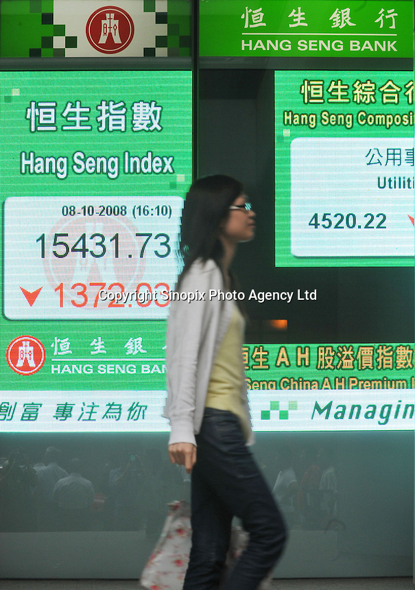 A woman walks pass a board indicating the Hang Seng Index rise of 1372 points in Hong Kong, a 9% lost of its value since the beginning of the American Financial Crisis triggered by the collapse of AIG. .