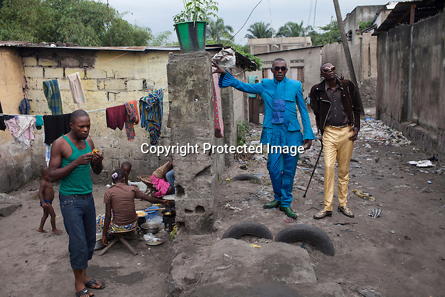 "KINSHASA, DEMOCRATIC REPUBLIC OF CONGO - FEBRUARY 12: Papa Griffe (L), a senior and a leader of the Sapeurs walks with his brother Jika in the Mombele area where they live area on February 12, 2012 in Kinshasa, DRC. The word Sapeur comes from SAPE, a French acronym for Société des Ambianceurs et Persons Élégants. or .Society of Revellers and Elegant People. and it also means, .to dress with elegance and style"". Most of the young Sapeurs are unemployed, poor and live in harsh conditions in Kinshasa,  a city of about 10 million people. For many of them being a Sapeur means they can escape their daily struggles and dress like fashionable Europeans. Many hustle to build up their expensive collections. Most Sapeurs could never afford to visit Paris, and usually relatives send or bring clothes back to Kinshasa. (Photo by Per-Anders Pettersson)"