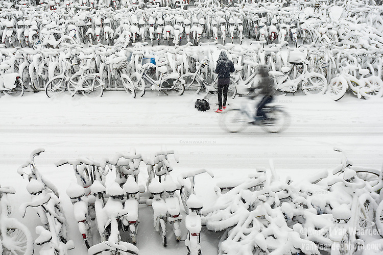 Snow covered bikes and riders in Amsterdam, the Netherlands.