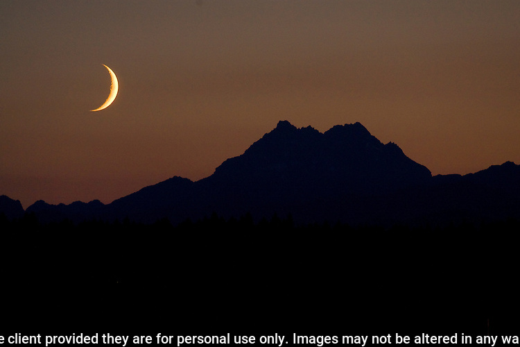 A waxing moon sets over the Olympic Mountains  on Friday, July 24, 2009. In the northern hemisphere, if the left side of the Moon is dark then the light part is growing, and the Moon is referred to as waxing (moving towards a full moon). If the right side of the Moon is dark then the light part is shrinking, and the Moon is referred to as waning (moving towards a new moon).  All RIghts Reserved. Jim Bryant.@2012