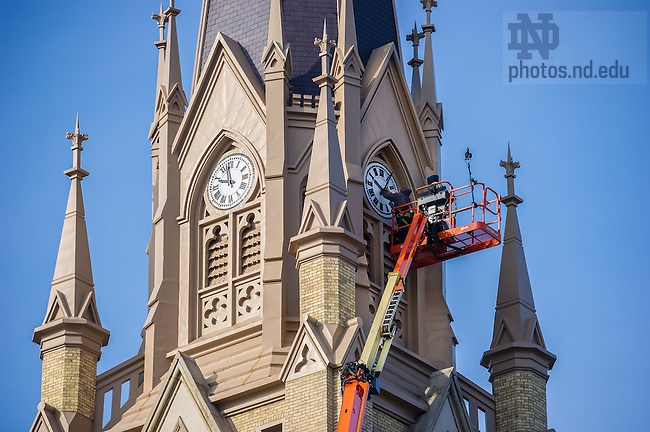 Mar. 18, 2014; L.J. Masters of Midland Engineering re-installs the minute hand of the north clock face on the Basilica.  The hand fell off at some point during the winter of 2013-2014.<br /> <br /> Photo by Matt Cashore/University of Notre Dame