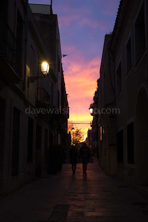 A couple walk into the winter Sunset in a Carrer de Negrevernís in Sarria, Barcelona, December 2nd 2017