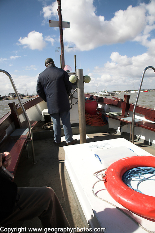 Ferryman steering ferry across River Deben between Bawdsey Quay and Felixstowe Ferry, Suffolk, England