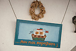 Wreath and hand-made sign with ferry boat: ...where are you going..., Chora, Anafi, Greece