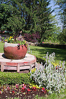 Huge container planter as focal point in garden on raised platform well pump, lawn grass, annual flowers, big trees, boxwood circular border, begonias, phormium, celosia, annuals and perennials