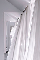 Contemporary bedrooms and bathrooms are concealed behind floor to ceiling white curtains at CasasNaAreia