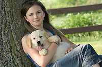 Teenage girl holding golden retriever puppy
