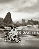 CHINA, Guilin, people traveling on a motorbike over a bridge in rural Guilin (B&W)
