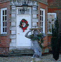 A Christmas wreath hanging on the front door is woven with a striking red ribbon and a wreath of leaves adorns the neck of the garden sculpture