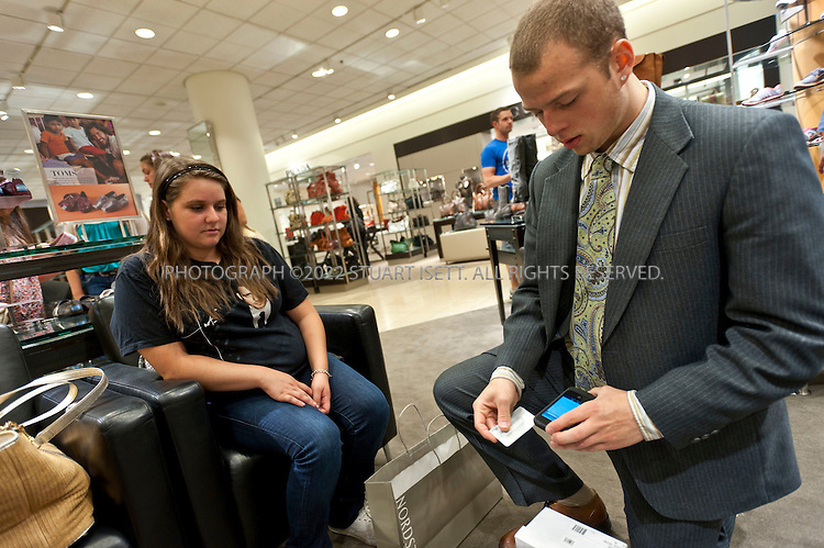 7/8/2011--Seattle, WA, USA..Jared Oboy (right), a salesperson at Nordstrom's downtown Seattle store, rings up a sale using a mobile device with a customer (no name given) by swiping a credit card through a reader attached to an iPod Touch Clerks at Nordstrom walk around with mobile devices iPod Touch and check out customers wherever they're sitting or standing, sending e-receipts...©2011 Stuart Isett. All rights reserved.