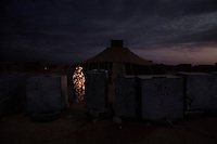 Sana Zrog, 19, student. Pictured beside water tanks in El Aaiun refugee camp, Algeria: 'When I was seven my parents told me we were living in a refugee camp, I was surprised and sad that I didn't know my homeland. I knew then that I didn't want to spend my life here or have my children here. When I was fifteen I started studying in Libya and now I am in university studying economics I am home now for a holiday but tomorrow I will fly back to Libya. Everything is free; the flight, accommodation, clothes, books, food, even toothbrushes, shampoo and some money every month. I say thank you to Libya for this, they help the Saharawis.'.