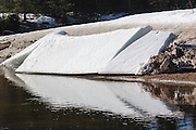 Large chuncks of ice on the riverbank of the Swift River during the winter months. This river travels along side of the Kancamagus Highway (route 112) which is one of New England's scenic byways in the White Mountains, New Hampshire USA