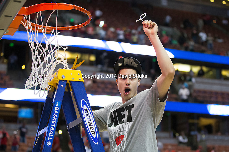 Wisconsin Badgers Bronson Koenig cuts down a piece of the net after the Western Regional Final NCAA college basketball tournament game against the Arizona Wildcats Saturday, March 29, 2014 in Anaheim, California. The Badgers won 64-63 (OT). (Photo by David Stluka)