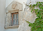 Window with a stone border and a face carved above the lace curtains in Bondo, a Swiss Bregaglia Valley town; the houses in Bondo date back to the 16th century