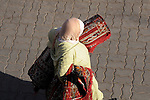 A woman carries rugs through the streets in Marrakesh, Morocco.